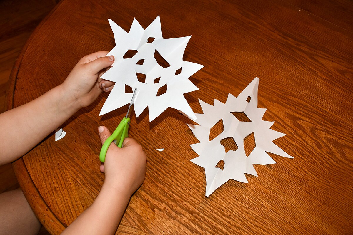 A child's hands cut out paper snowflakes.
