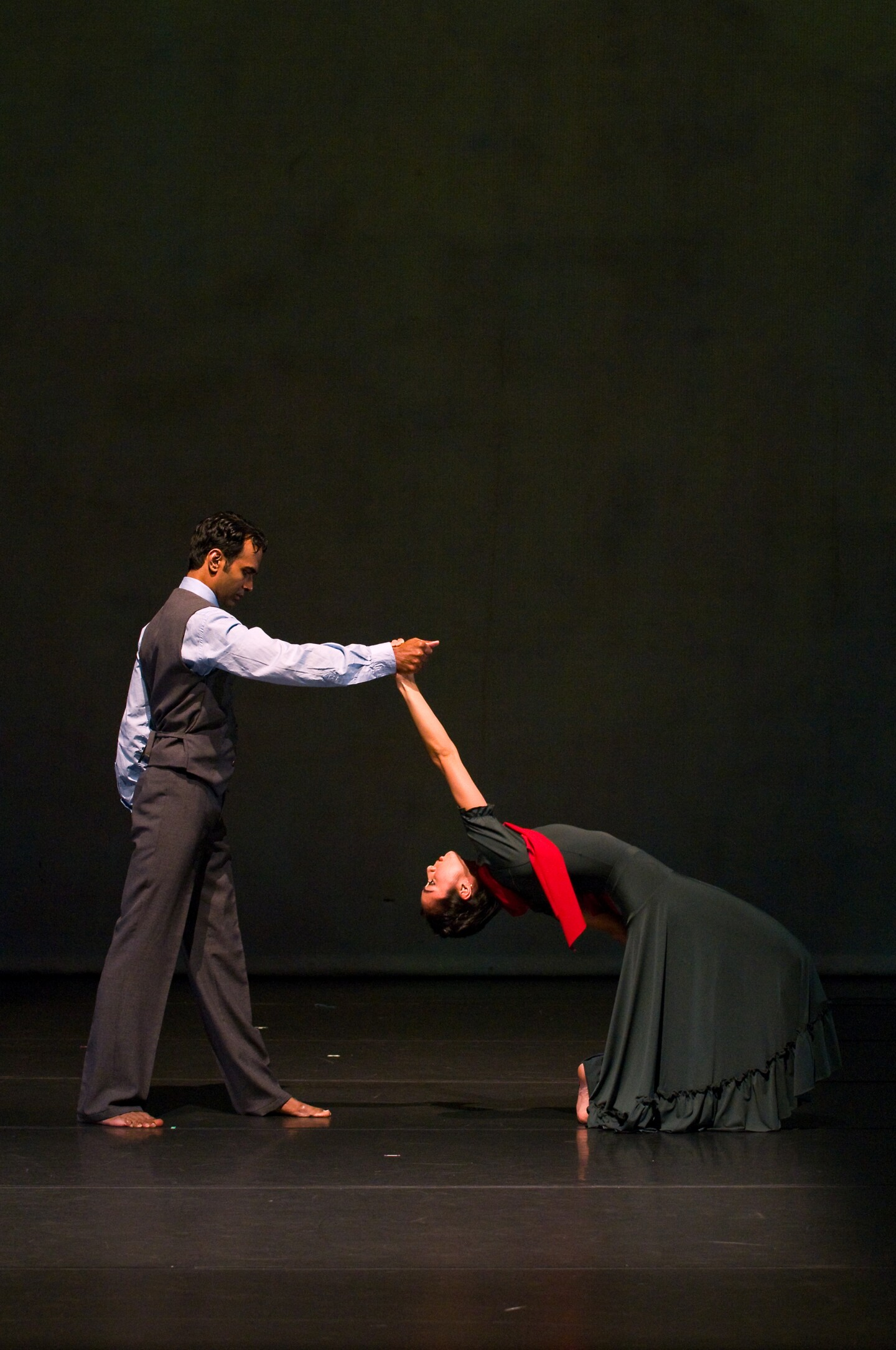 A barefoot man and woman dance together.