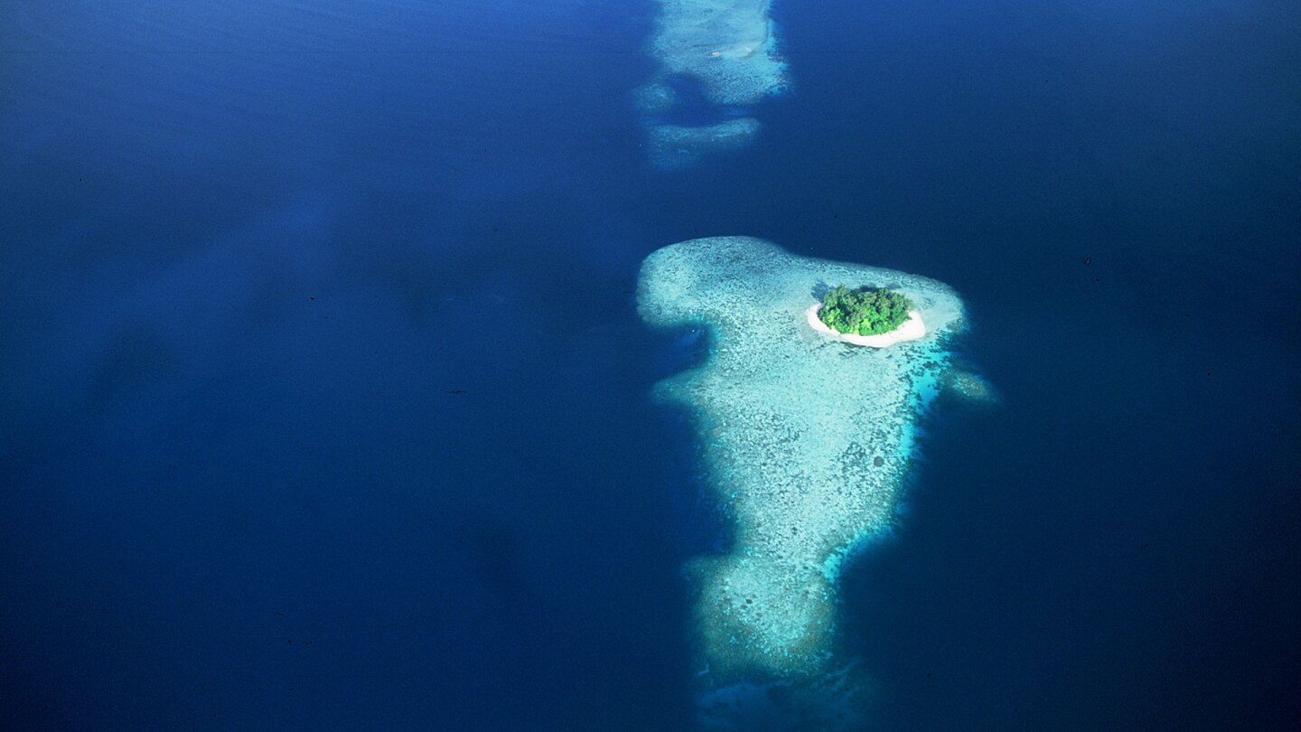 """Overhead shot of an island in the middle of a vast ocean. 