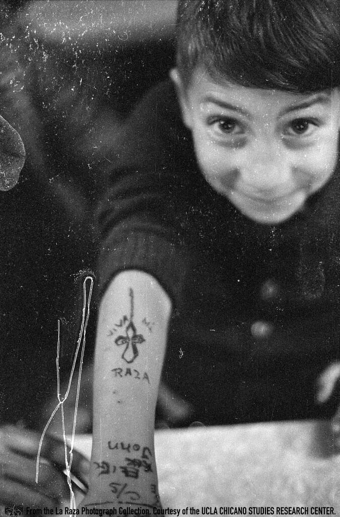 """CSRC_LaRaza_B14F3S1_N035 Child holds out his arm inside a restaurant with the words """"Viva mi raza."""" 