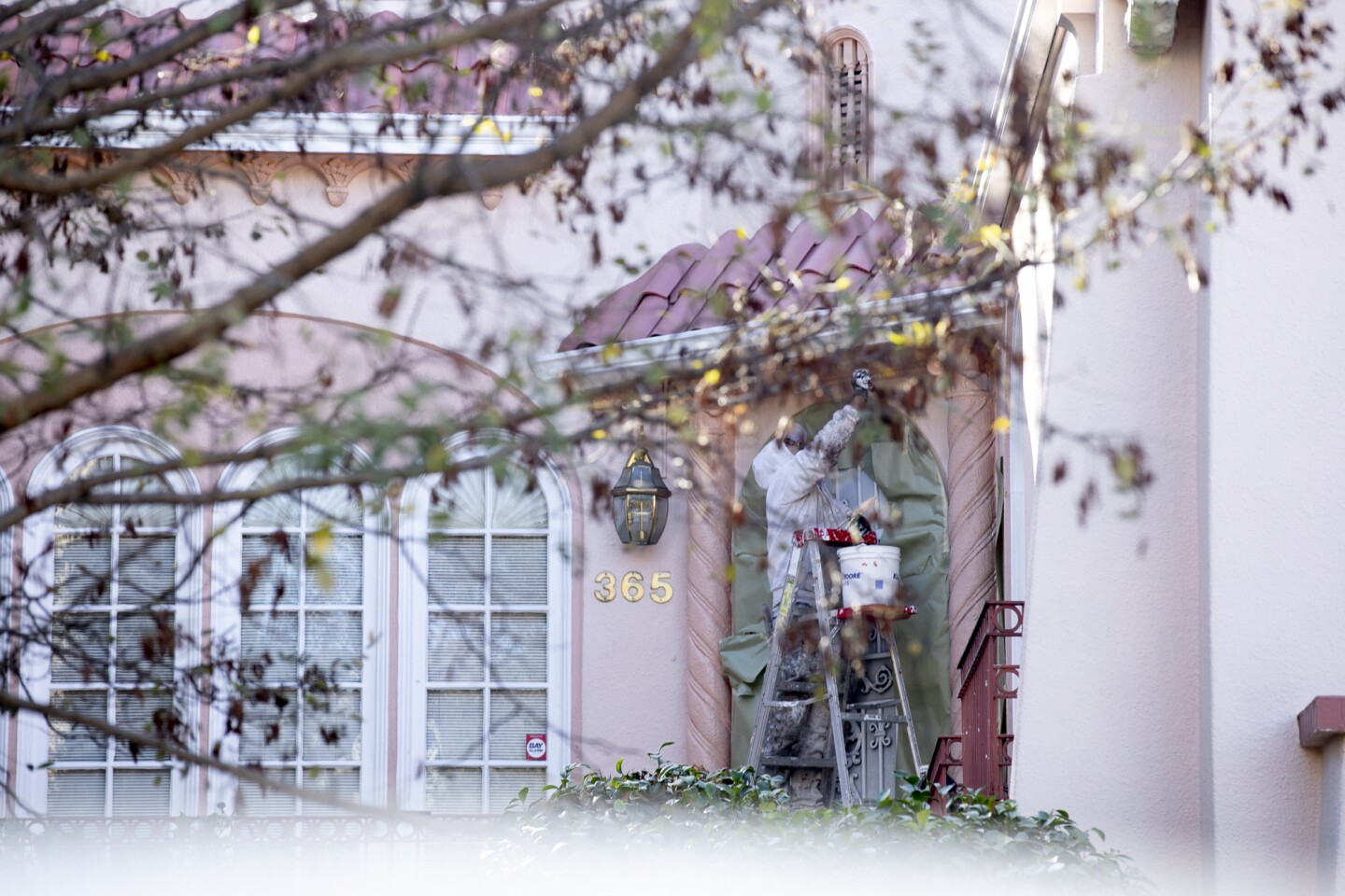 A man in coveralls stands on a ladder as he paints a house's exterior