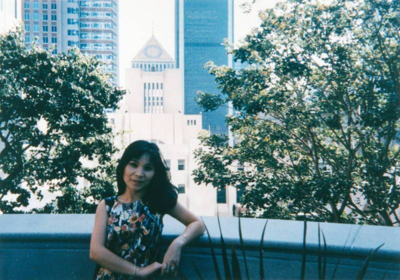 A woman poses in a terrace in front of a tall building and two trees.