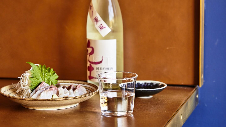 A cup of ginjo sake paired with Tsubaki's kanpachi sashimi