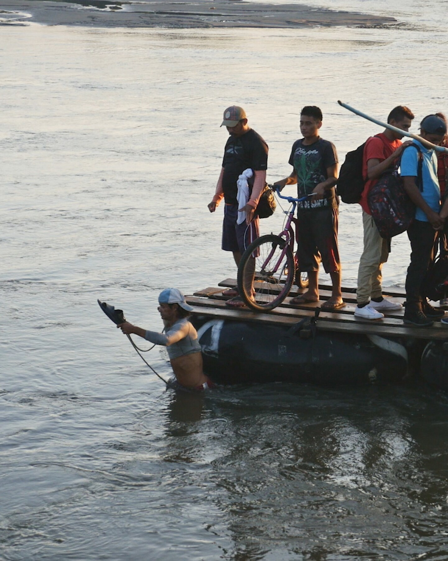 """Migrants cross a river on a raft.   Still from """"Global Mosaic"""" film """"Migrant Journeys"""""""