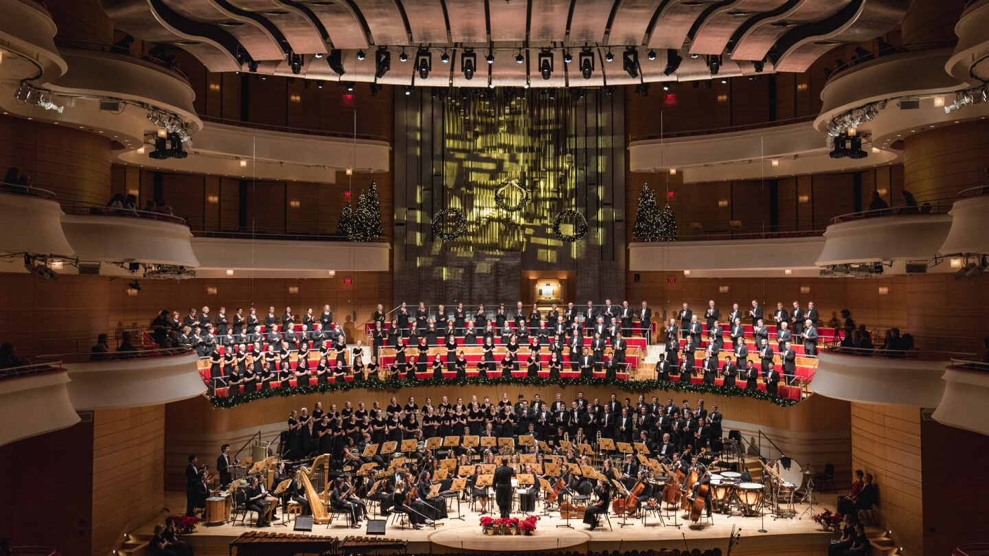 "A wide-angle shot of a concert hall with an orchestra on stage. | From ""All is Bright: A Concordia Christmas"" 