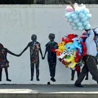 Street vendor walking by a mural depicting children holding hands on W. Temple St. (Photo by Ricardo Dearatanha/Los Angeles Times via Getty Images)