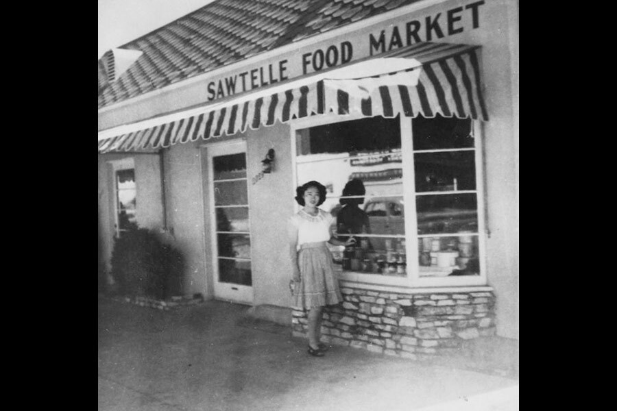 Black and white photo of a Japanese American woman standing in front of the Sawtelle Food Market, circa 1947