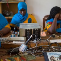 A group of women in Zanzibar sits at a table full of electric eqiupment.   Nicky Milne/Thomson Reuters Foundation