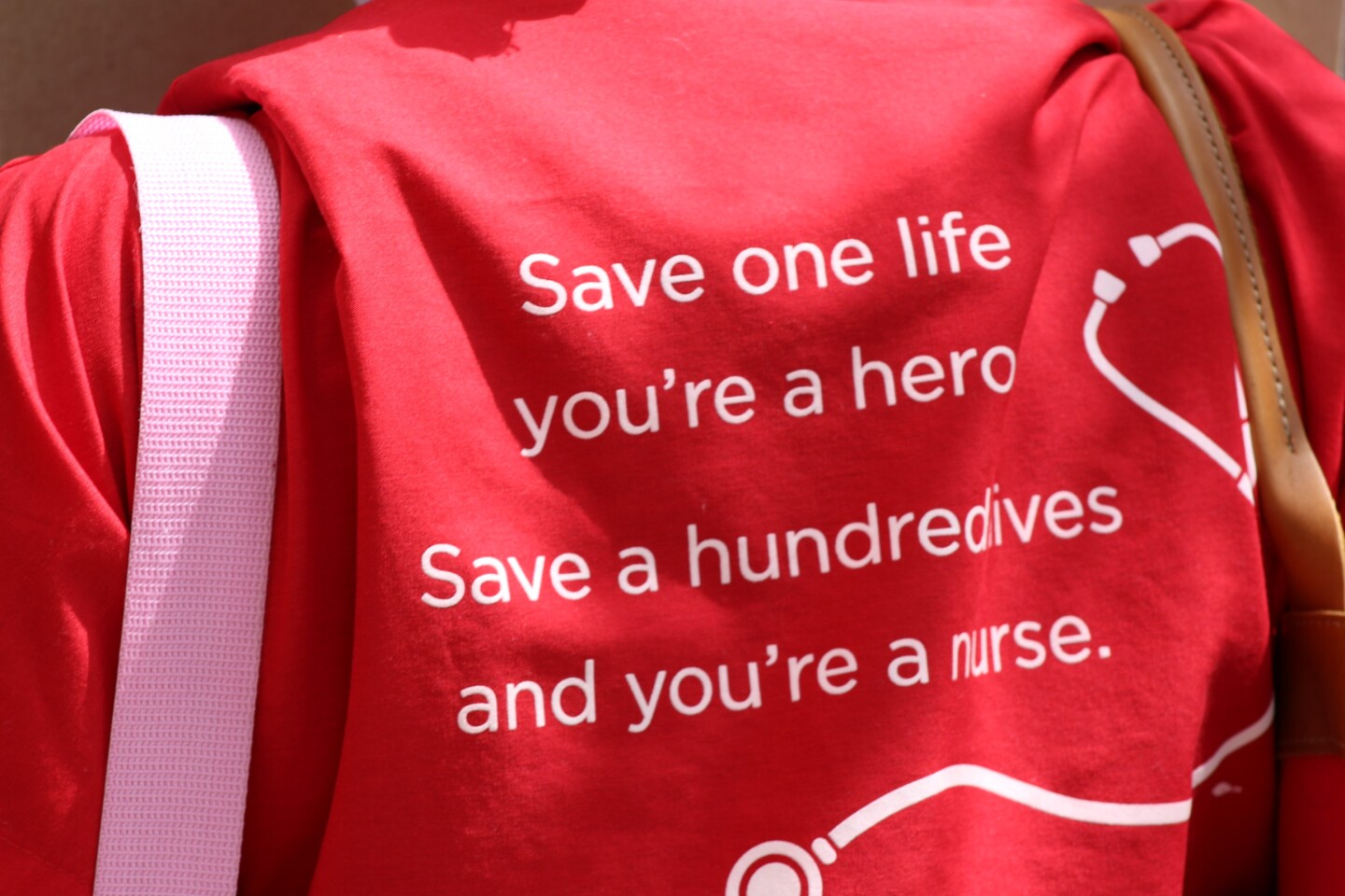 "Back of someone's shirt reading, ""Save one life, you're a hero. Save a hundred lives, you're a nurse"" during protest on Friday April 3rd 