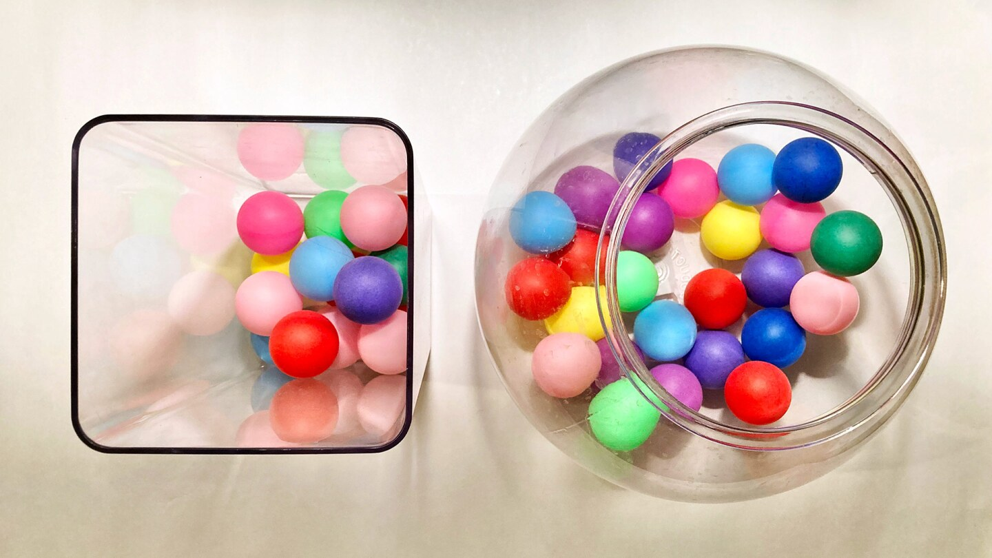 Two clear plastic containers with different quantities of colorful ping pong balls in them.