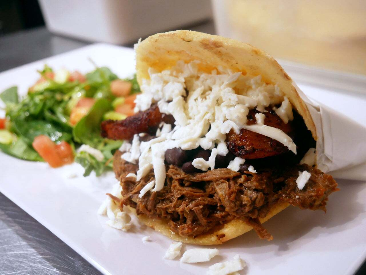 Pabellón arepa is filled with shredded cheese, sweet plantains, black beans and crumbled cheese | Courtesy of Cariaco
