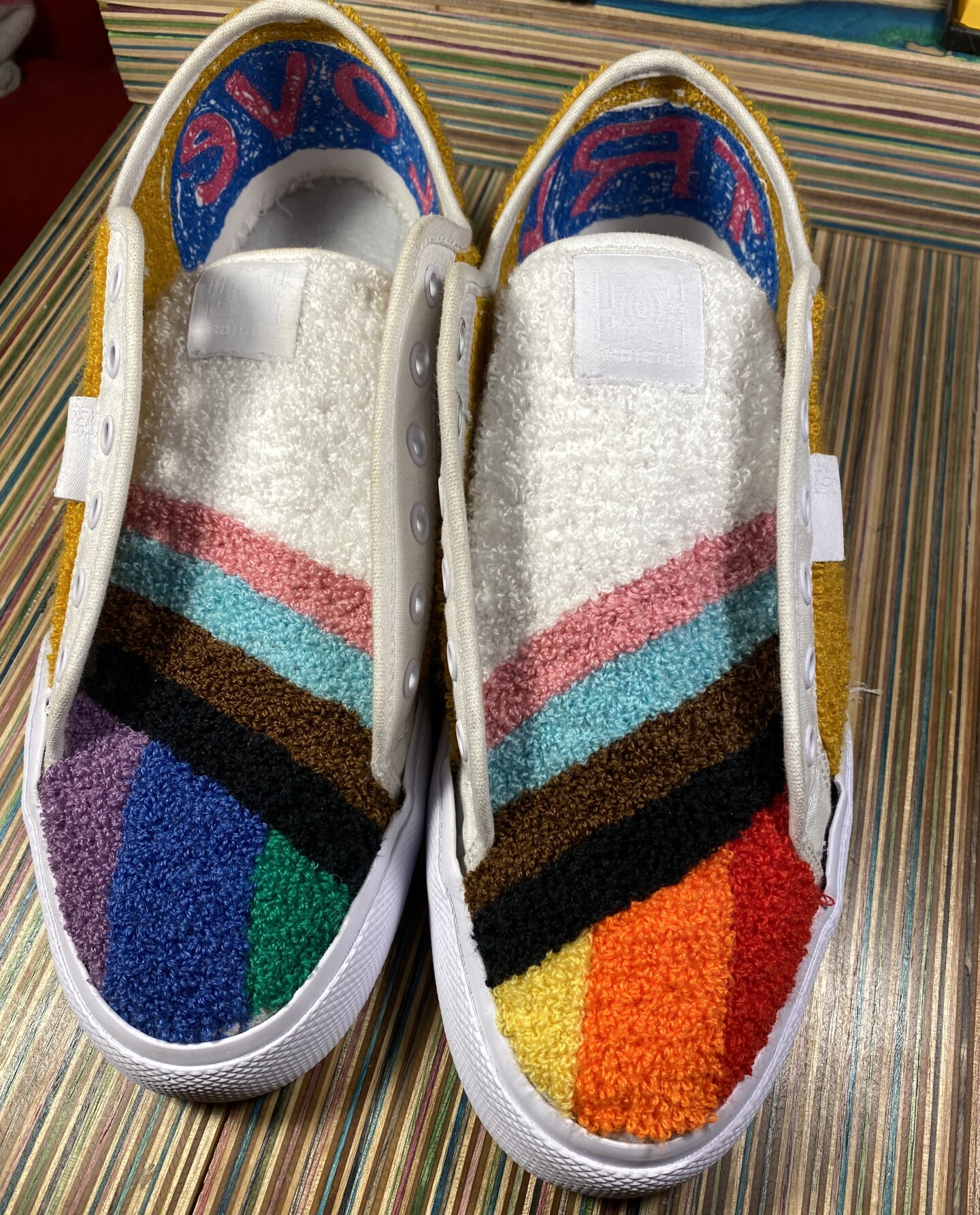 A pair of skater shoes chenille embroidered with the LGBTQ rainbow pride flag. The shoes are sitting on top of a multicolored striped surface.