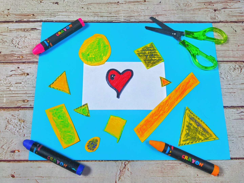 Un pedazo de papel azul con recortes de varias figuras geométricas diferentes rodeadas de crayones y unas tijeras verdes.