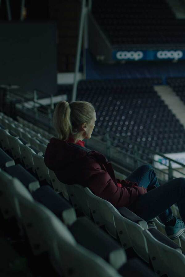 "Helena, played by Ane Dahl Torp, sits in an empty stadium staring out at the field. | ""Home Ground"""