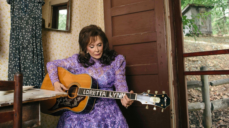Loretta Lynn plucks at her guitar.