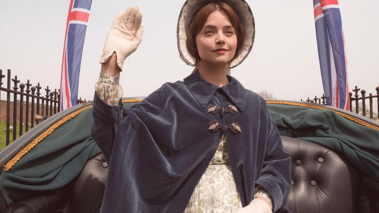 """Queen Victoria (Jenna Coleman) raises her hand from her seat in a carriage. 