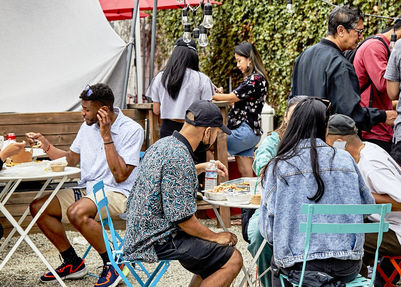 Attendees gather around outdoor tables to eat their purchases at the FilLed Market. Nearby is a tall wall covered in green vining plants.