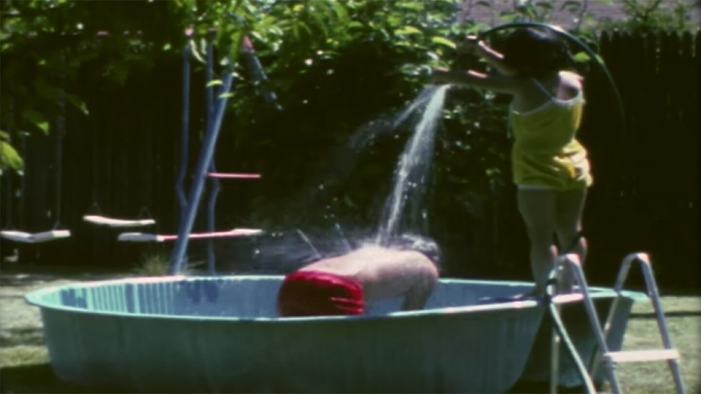 "Two children playing in the pool in the backyard | Still from Gee Family home video from CAAM's ""Memories to Light"" project"