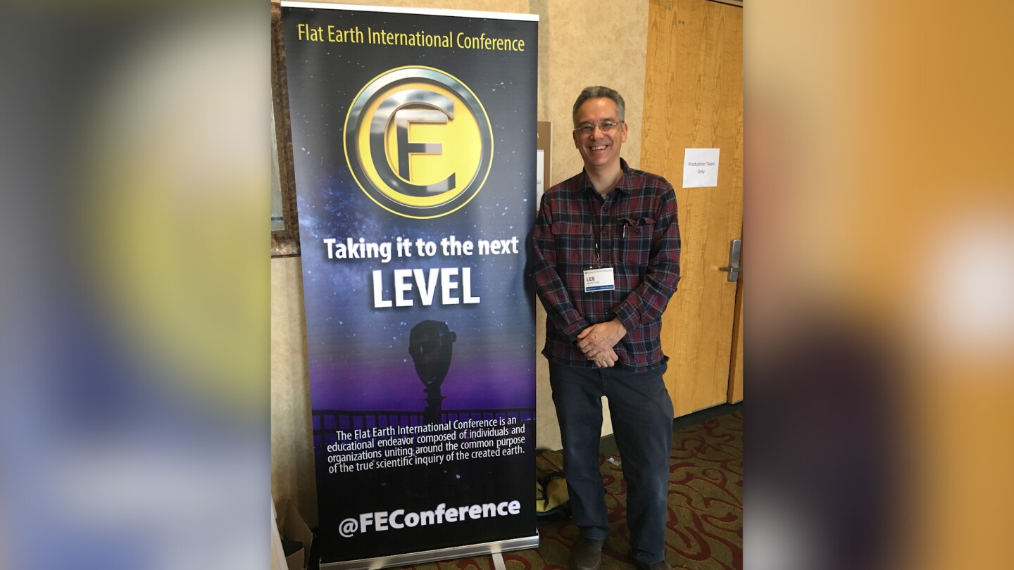 Lee McIntyre poses next to a poster promoting a flat earth conference.