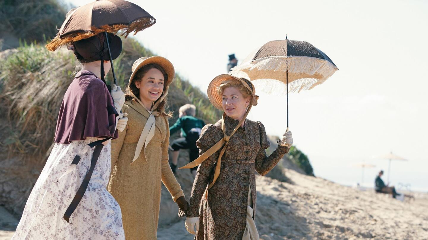 """Three women at the beach wearing bonnets and holding parasols. 