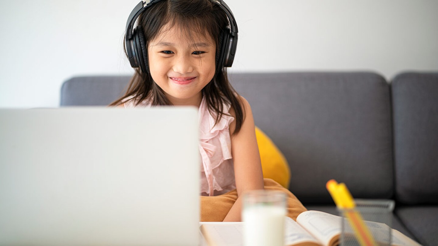A small child smiled as she works in front of a computer. | iStock
