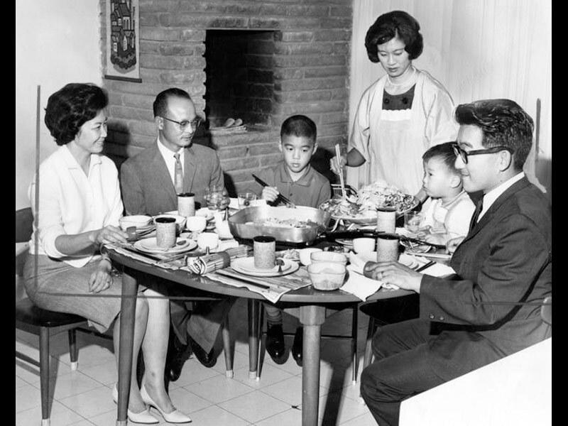 Black and white photo of Mrs. Yoshida as she begins preparing batayaki for Mr. and Mrs. Joe Ikuta and their children, Ronnie, Douglas and Yoshida, 1963