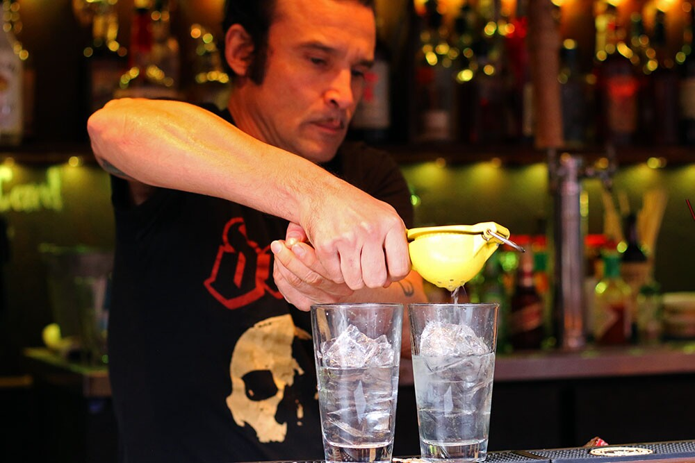 A bartender squeezes a fruit into two drinks.