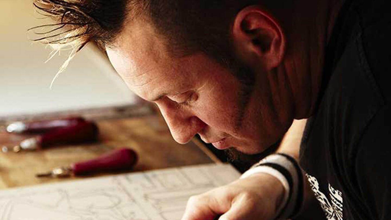 Dave Lefner carving details out of design on linoleum; Photograph by Prakash Shroff | Courtesy of the artist