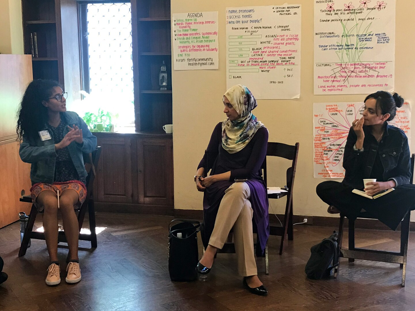 Three women sit together in discussion