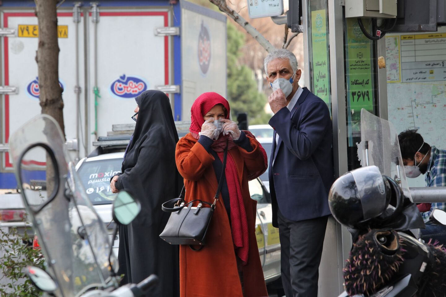 People wearing protective masks wait along the side of a street in the Iranian capital Tehran on February 24, 2020