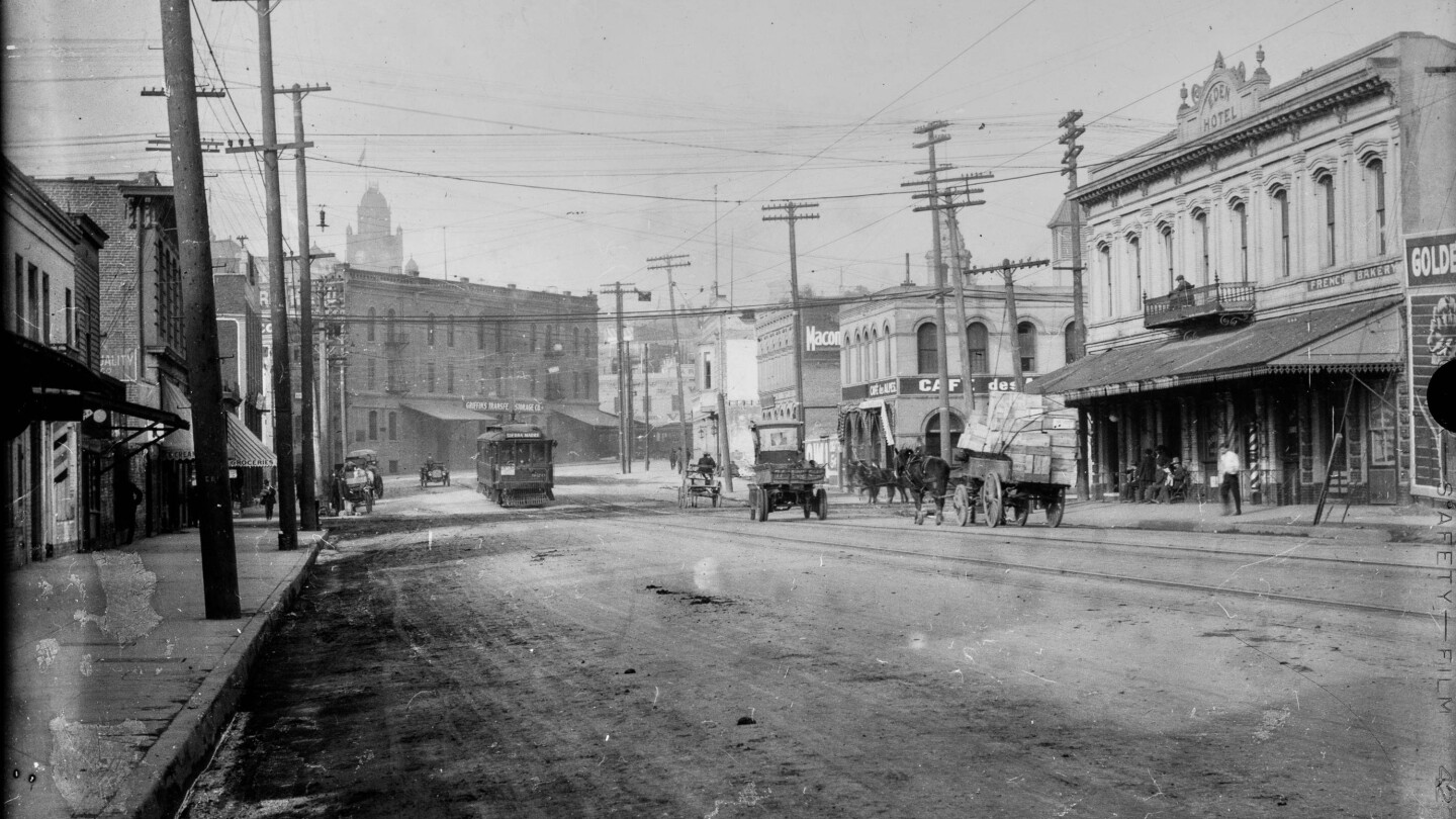 "An image of the French district in downtown Los Angeles. The image shows Aliso Street in downtown Los Angeles, California, with signs labeling buildings ""Griffins Transfer and Storage Co."" and ""Cafe des Alpes"" next to ""Eden Hotel,"" which are located on opposite corners of Aliso and Alameda Streets. A Pacific Electric streetcar sign reads ""Sierra Madre"" and automobiles and horse-drawn wagons are seen in the dirt road."