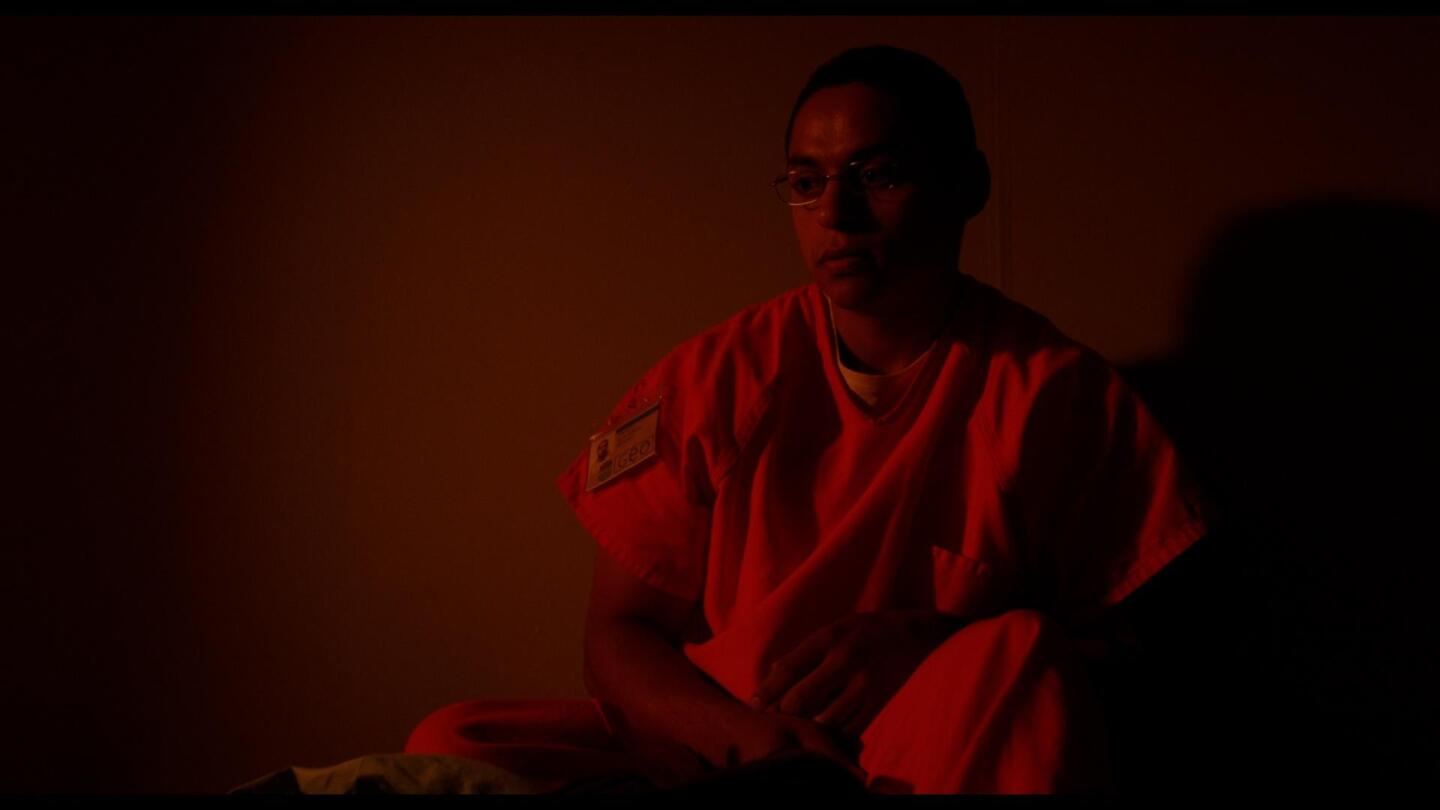 """A man in prison uniform sits in a dark room. 