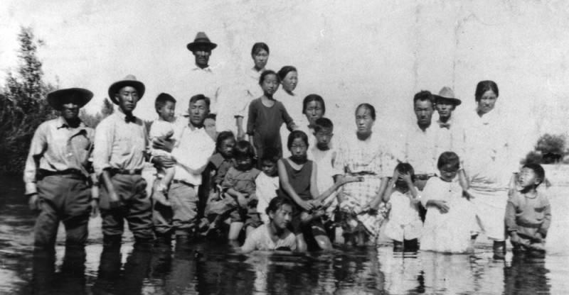 Black and white photo of a Korean American family posing during a trip to a California river, circa 1900