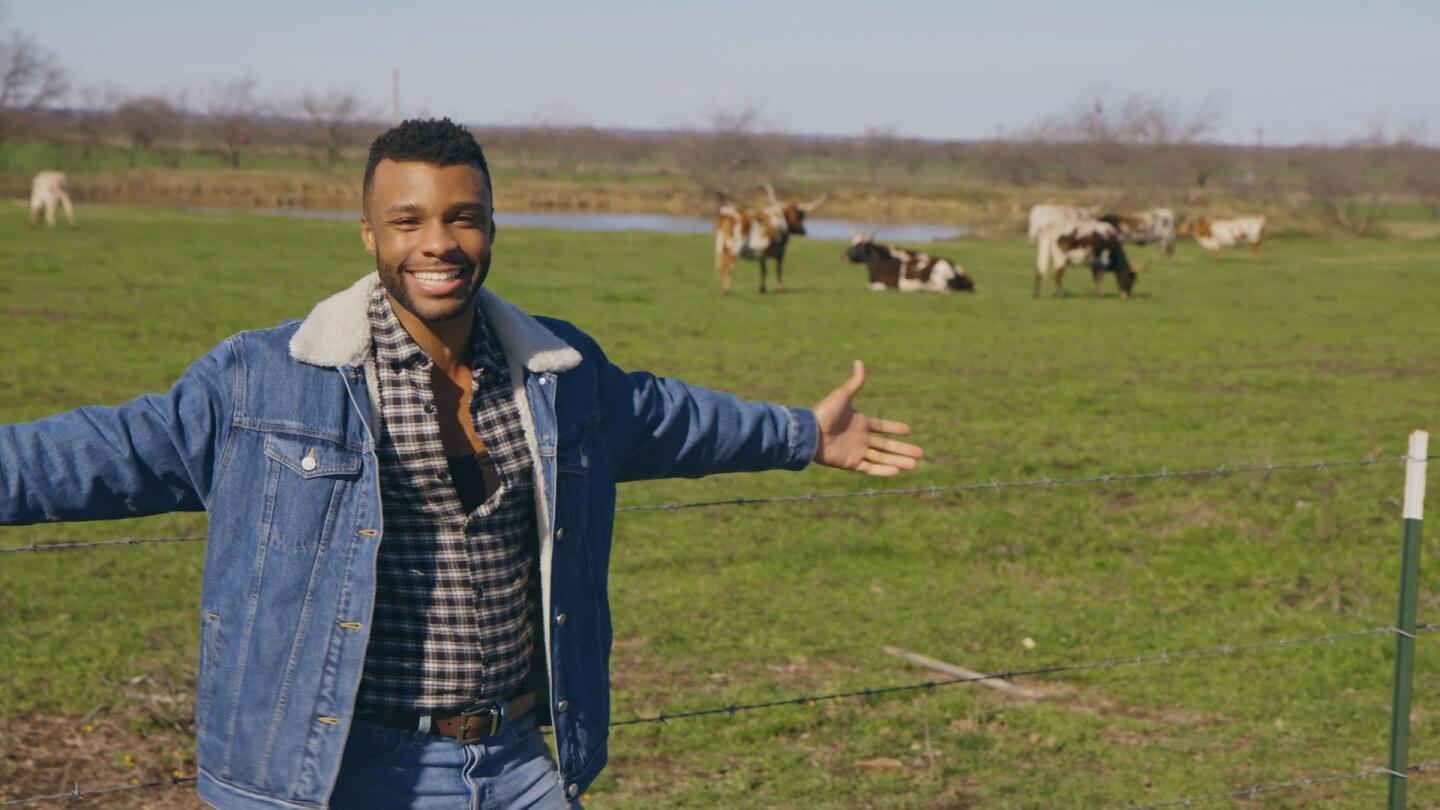 """Dyllón Burnside in a pasture with his arms outstretched. 