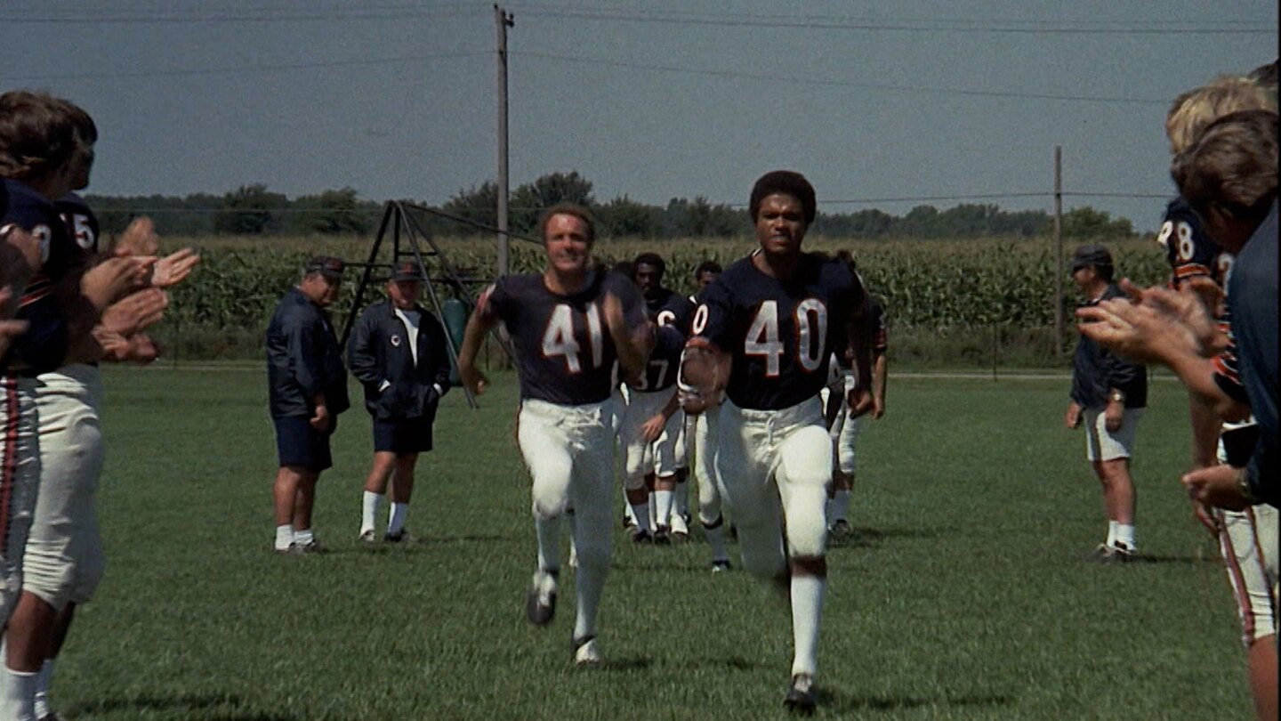 "Football players running on a field. | From ""Brian's Song"""