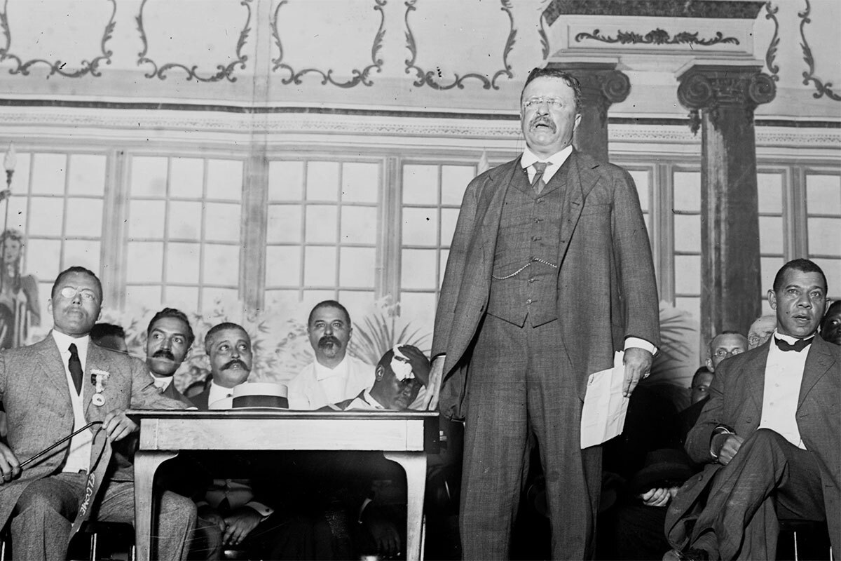 "Theodore Roosevelt (foreground) stands on stage before an audience with Booker T. Washington sitting behind him. | Still from ""City Rising: The Informal Economy"""