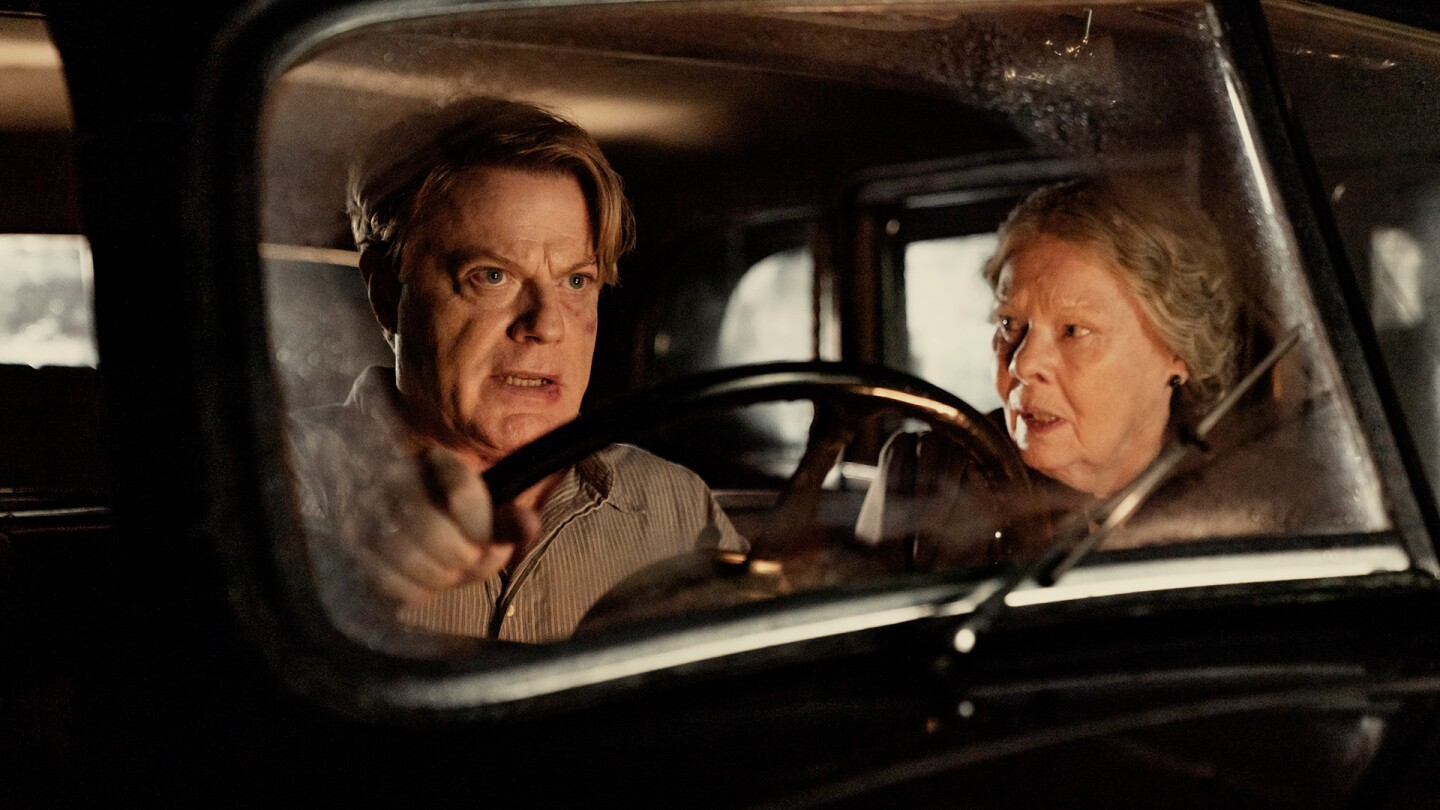 "Eddie Izzard and Judi Dench sitting inside a vehicle in their roles in ""Six Minutes to Midnight."""