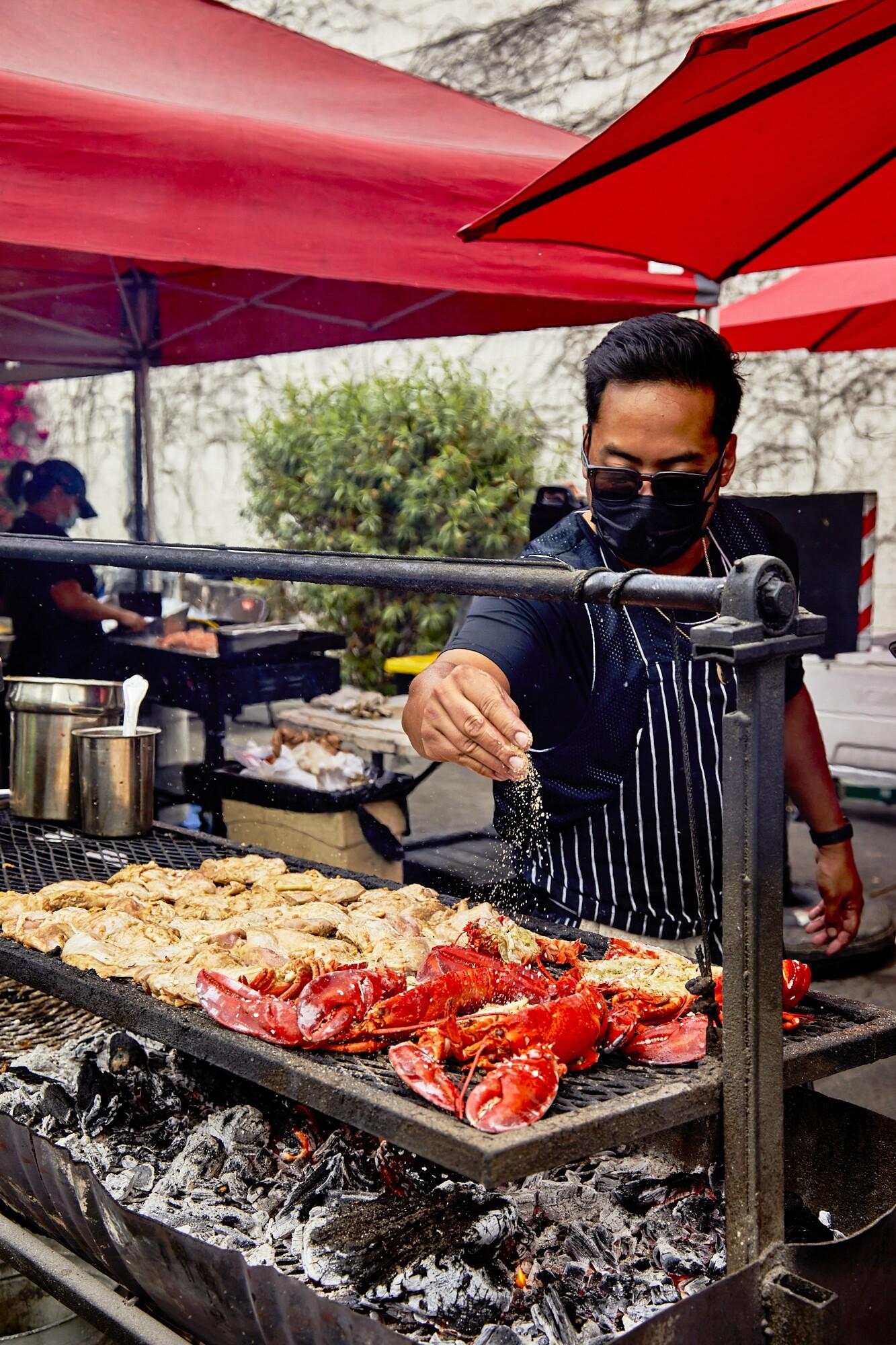 Johnny Angeles seasons lobsters at Lobsterdamus. He stands beneath red umbrellas.
