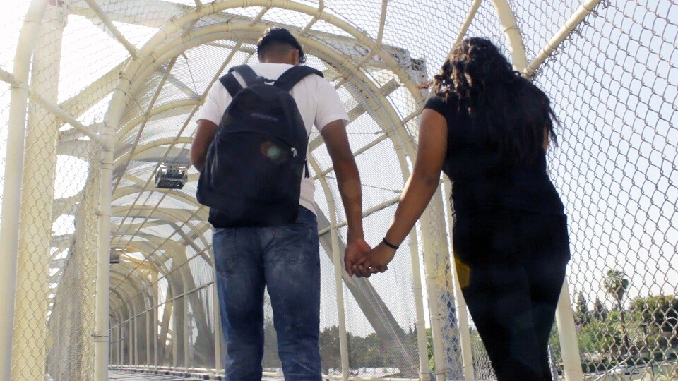 Roots Raices: Young Couple Holding Hands on Bridge