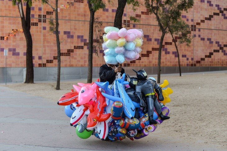 Street vendor Lucas Tax sells inflatable toys and cotton candy outside the California Science Center at Exposition Park in Los Angeles on March 24, 2019. | Agustin Paullier/AFP via Getty Images