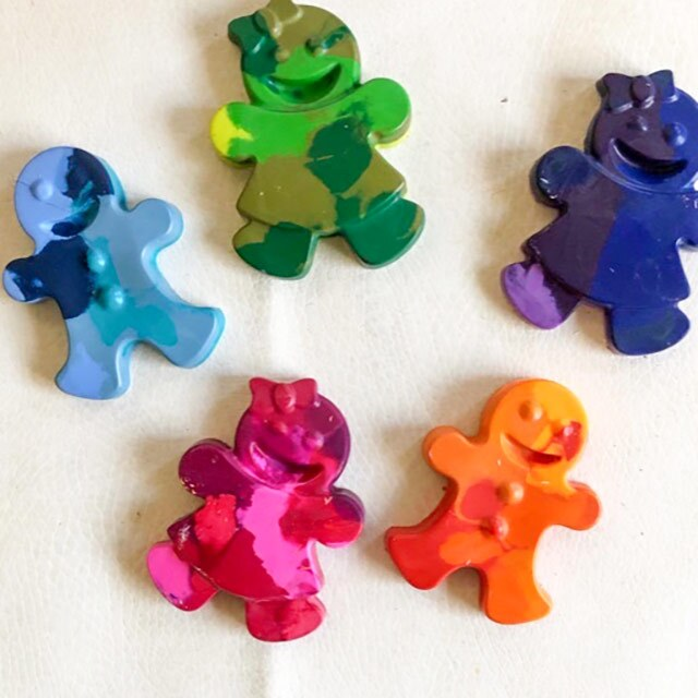 Five swirled crayons in the shape of gingerbread dolls in blue, orange, purple, pink and orange shades.