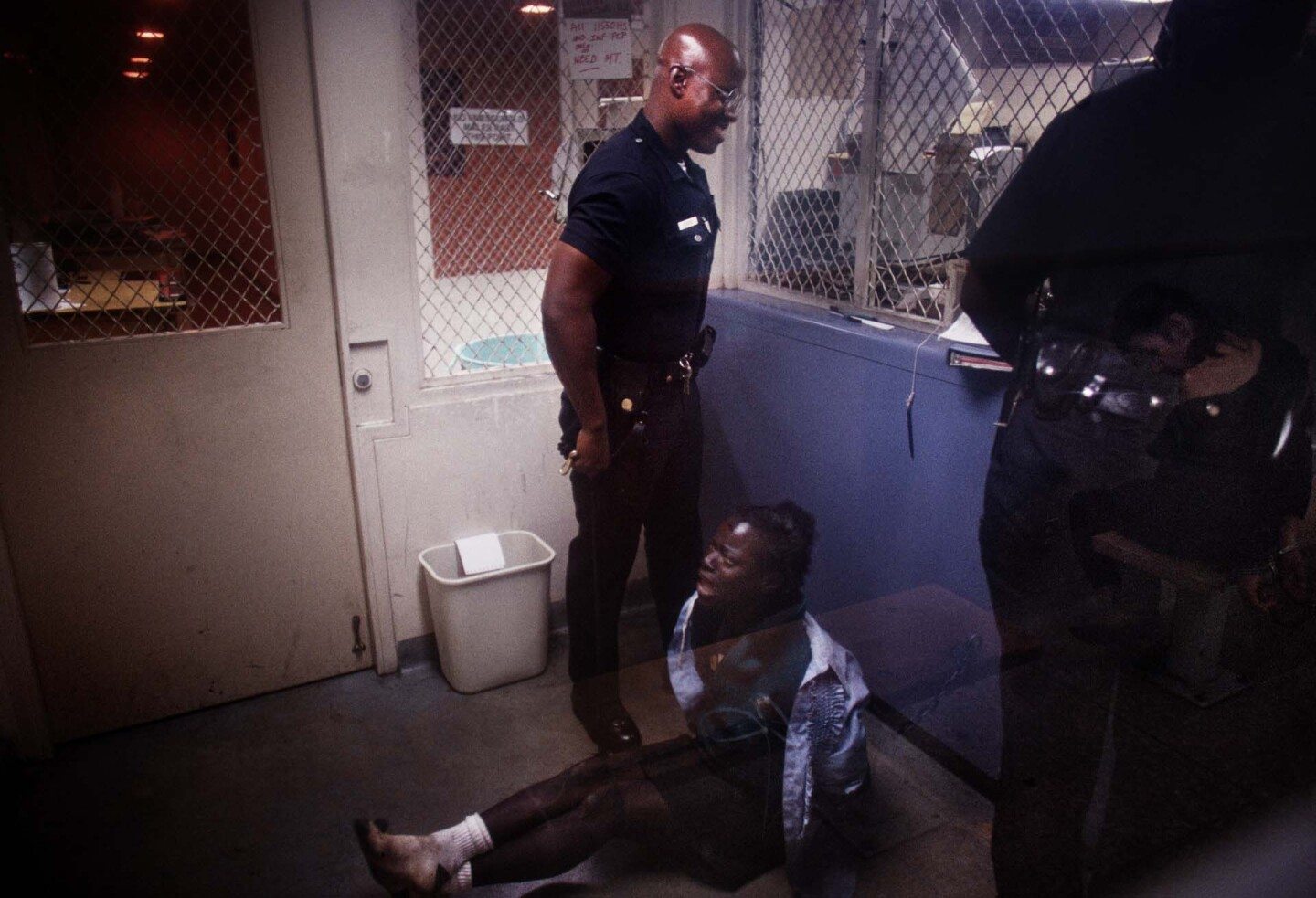 A handcuffed woman is detained and booked at Rampart Station. | Joseph Rodriguez
