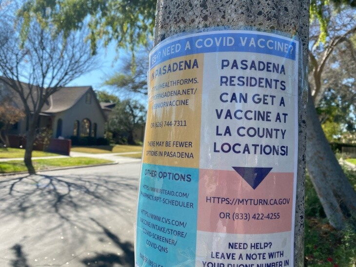 A sign on a lamppost in a residential area advertises how and where Pasadena residents can get vaccinated.