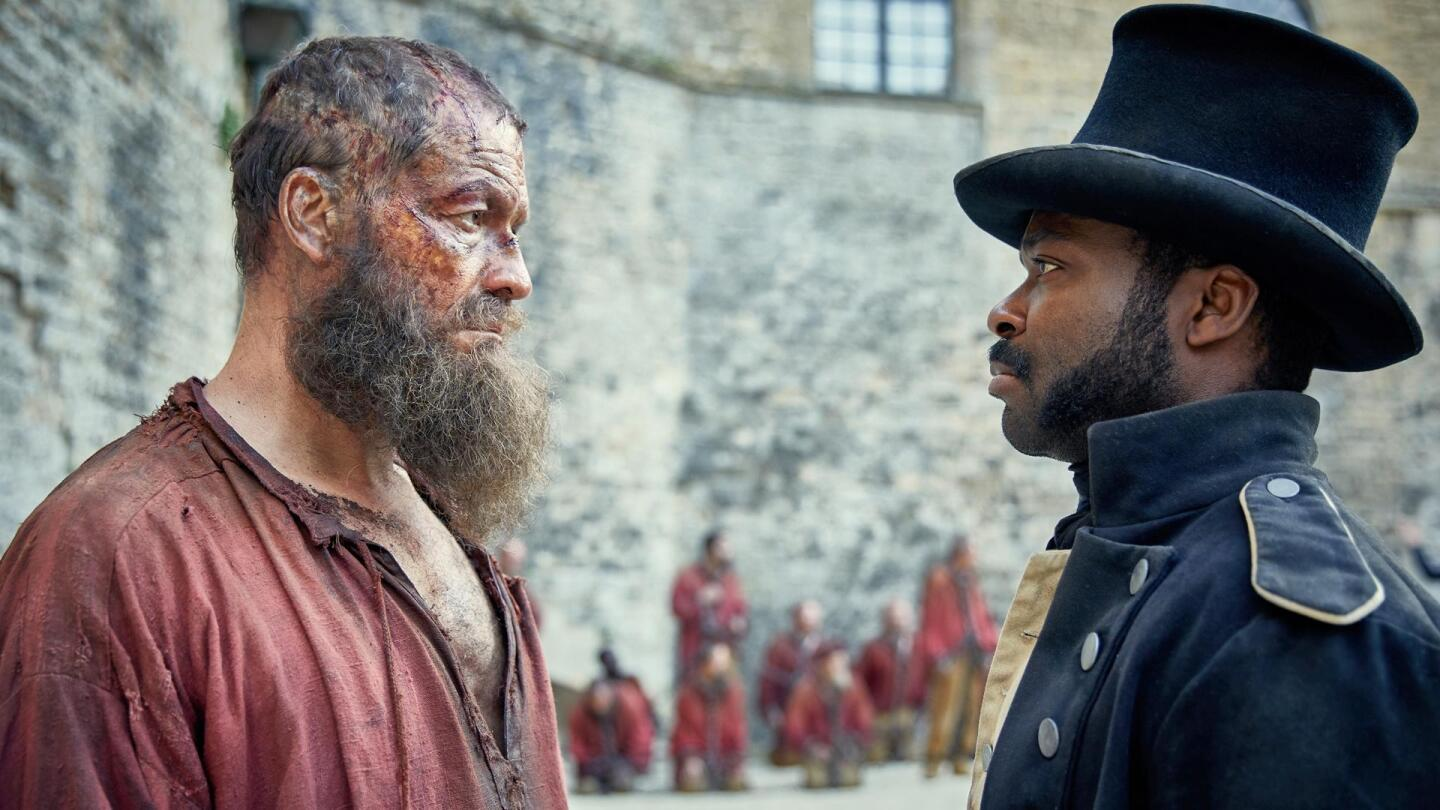 David Oyelowo as Javert (right) faces a rugged, bearded man.
