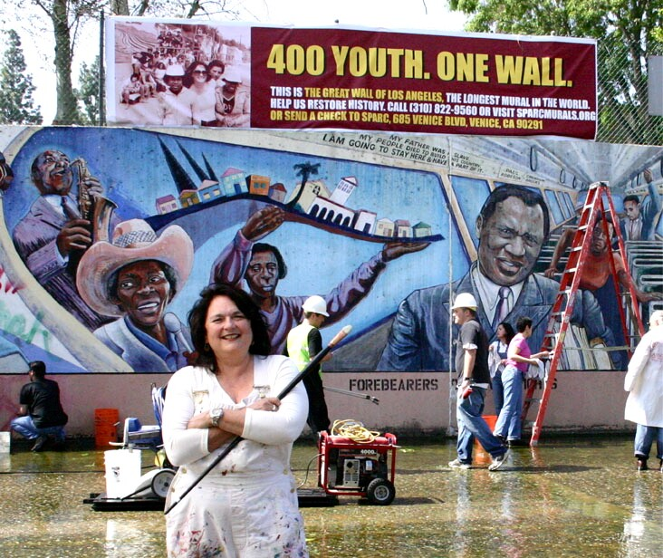 "Judy Baca poses in front of the ""The Great Wall of Los Angeles 1950: Forebearers of Civil Rights"" panel at the Tujunga Wash in the San Fernando Valley."