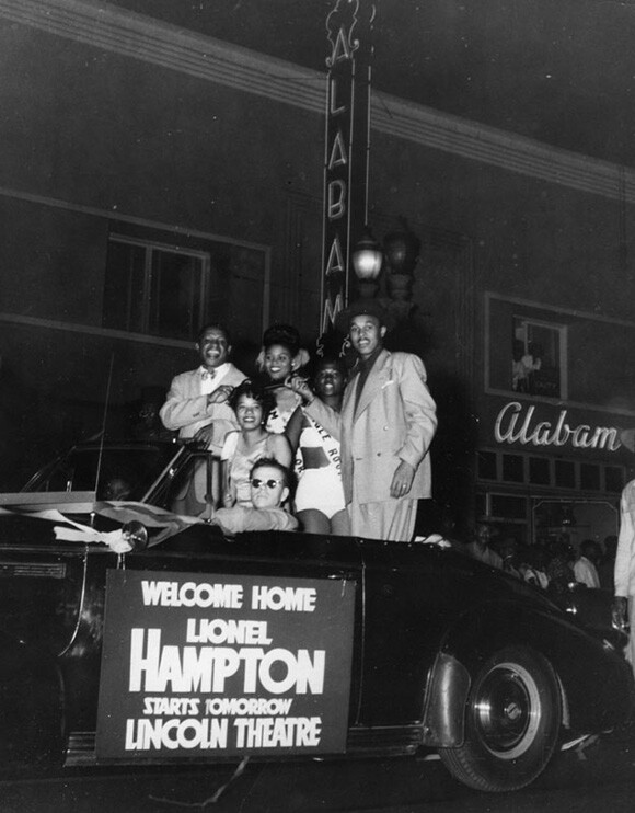 Lional Hampton, at far left, rides in a Cadillac convertible in front of Club  Alabam  on Central Avenue, a busy thoroughfare of businesses, nightclubs, and homes in Los Angeles. | Courtesy of the Los Angeles Public Library