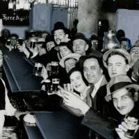 Men and women raising their glasses at a bar | Los Angeles Examiner Photographs Collection, University of Southern California Libraries