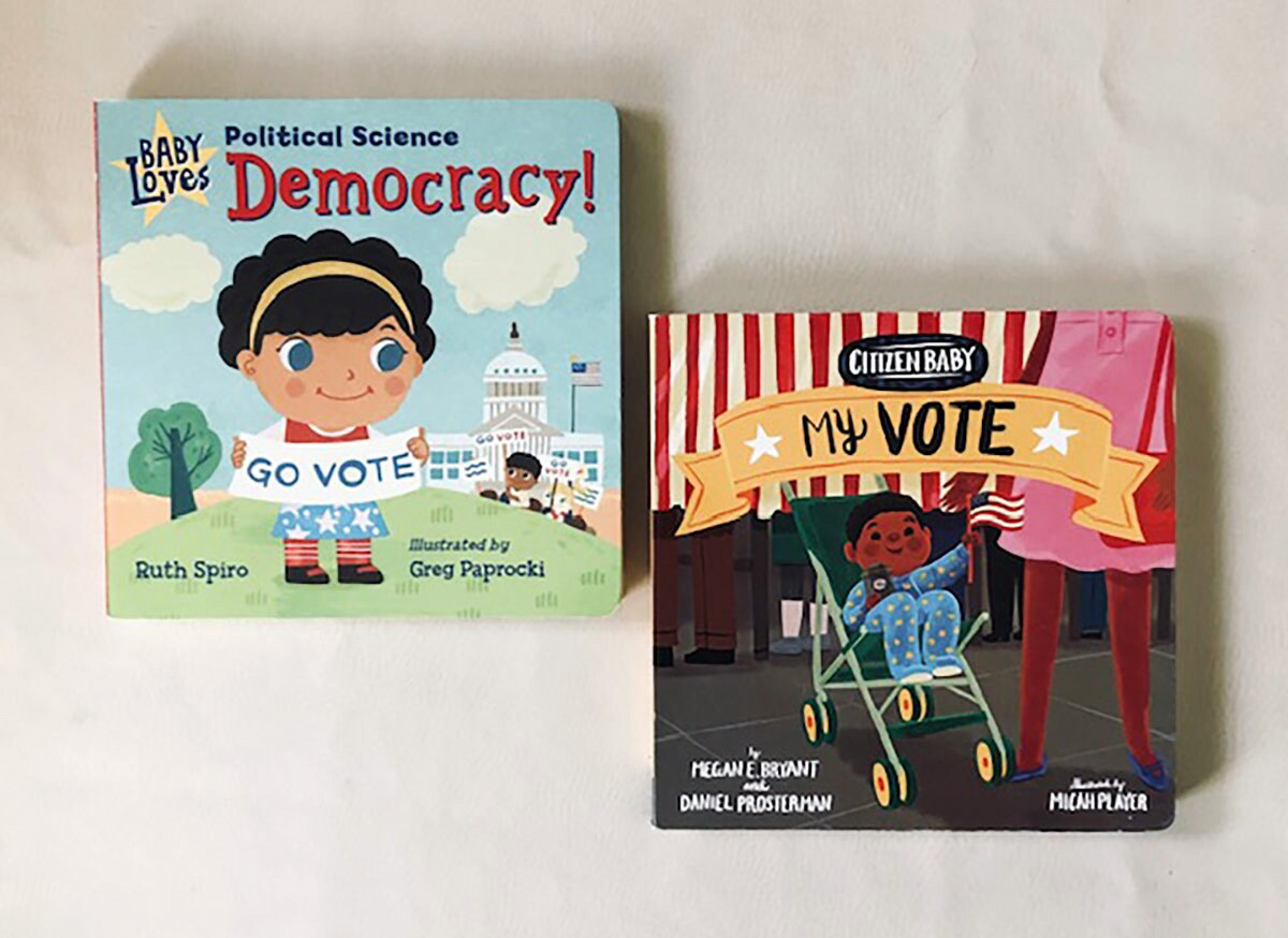 "Book covers of ""Baby Loves Political Science: Democracy!"" featuring a small child cartoon holding a sign that reads ""go vote"" and of ""Citizen Baby: My Vote"" featuring a cartoon baby in a stroller."