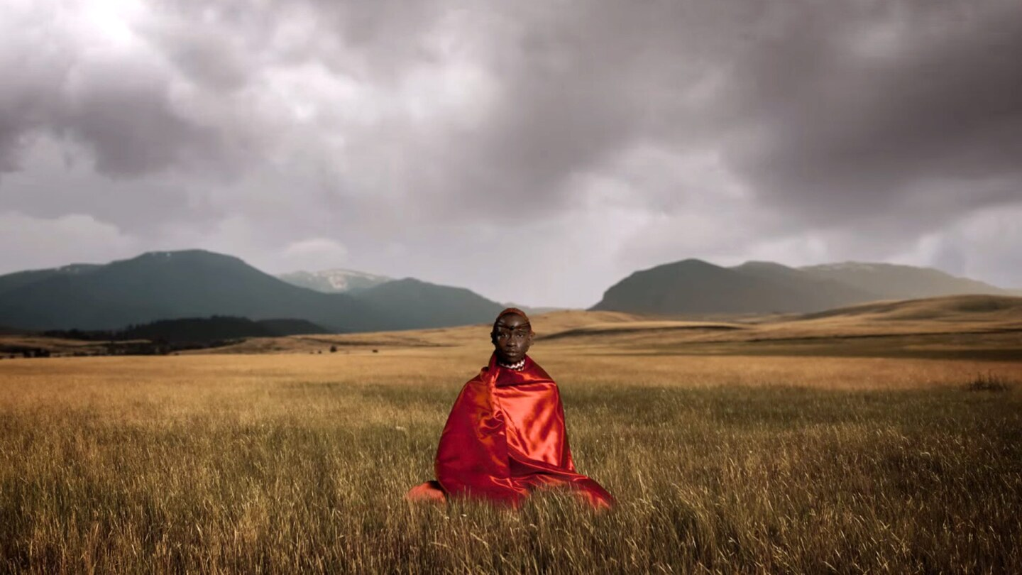 Still from Border Blaster Music Video: A person in red clothing in tall grass.