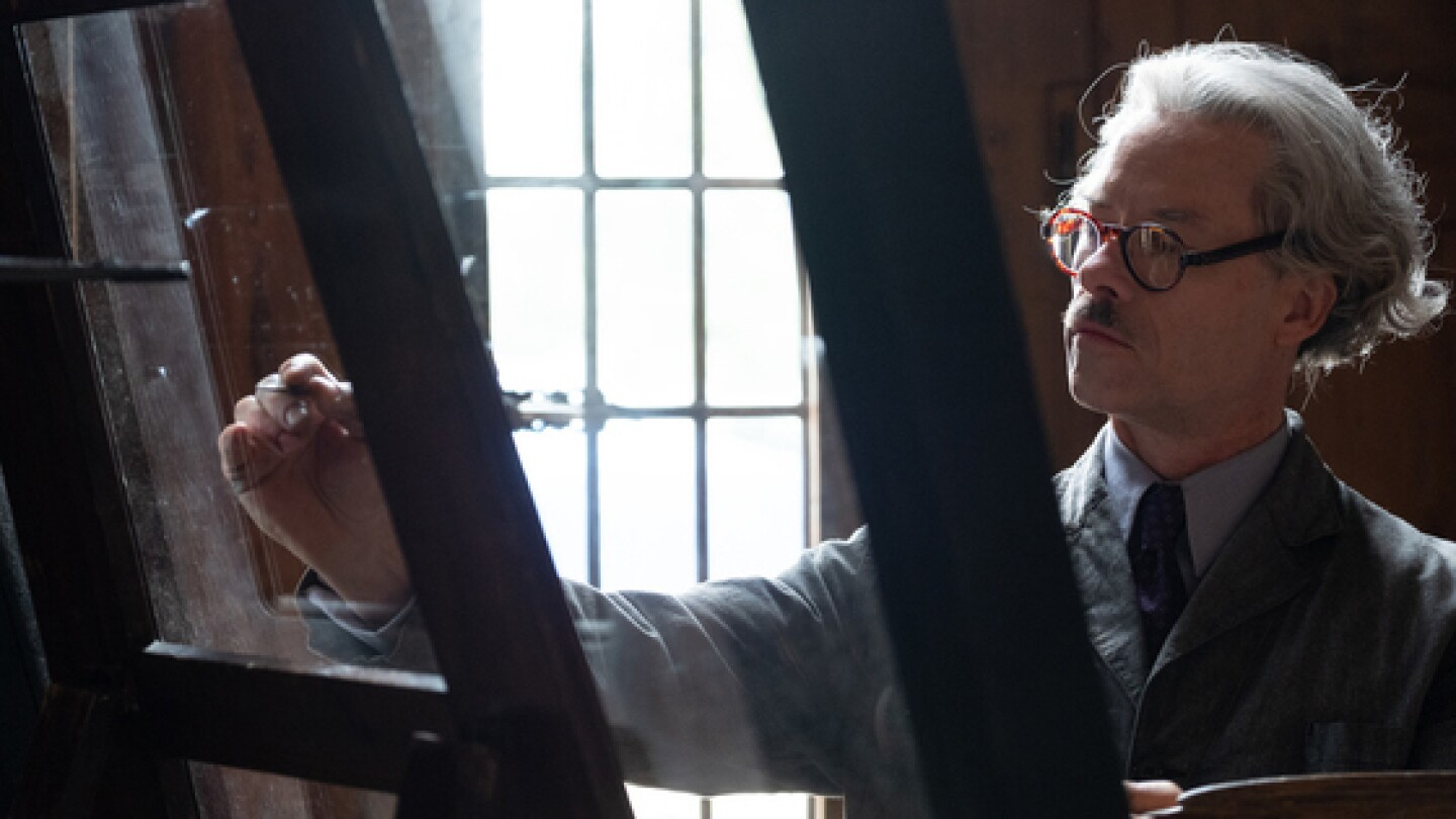 """A man paints on an easel. 